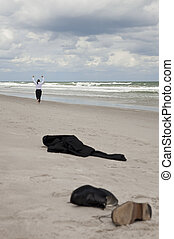 Concept shot showing a businessman leaving his clothes on a beach and running arms raised towards the sea