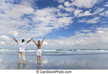 Man and Woman Couple Celebrating Arms Raised On A Beach