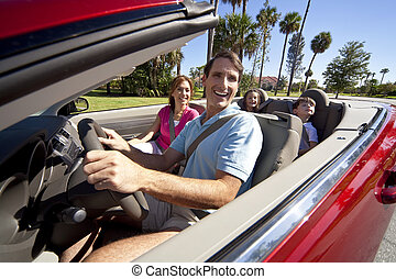 Family Driving In Convertible Car - A family of four,...