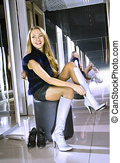 woman fits on white boots in a boutique