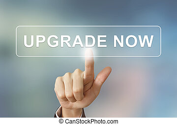 business hand clicking upgrade now button on blurred...
