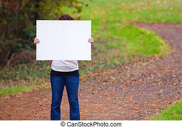 Holding White Sign - An anonymous girl holds a large white...