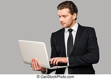 Businessman with laptop Confident young man in formalwear...
