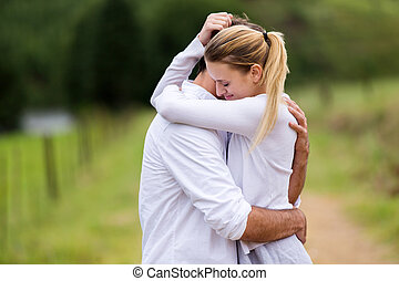 young couple hugging - loving young couple hugging outdoors