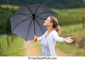 woman with arms open holding umbrella