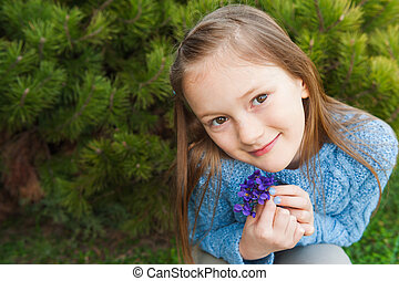 Close up portrait of a cute little girl, holding small...