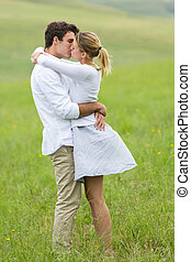 young couple kissing on green field - beautiful young couple...