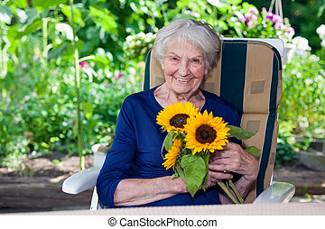 Happy Old Lady Sitting on Chair Holding Sunflowers - Close...