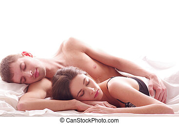 Young loving couple in the bed isolated on white