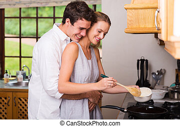 young man hugging girlfriend while she cooks for breakfast -...