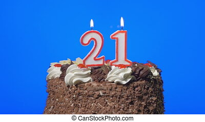 Blowing number 21 candles on a cake