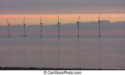 Ocean wind turbines af dawn - Huge ocean wind turbines at...