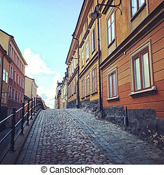 Cobblestone street with old buildings in Stockholm -...