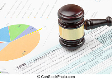 Wooden judge's gavel over 1040 US Tax form and colorful...