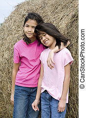 Two young girls standing against haybale