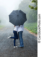 young couple hiding behind the umbrella - romantic young...