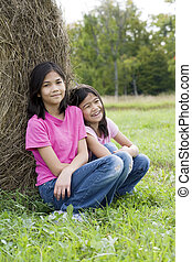 Two young girls sitting against haybale