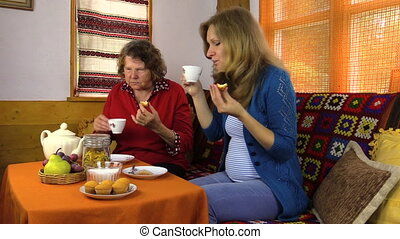women eat sweets with tea - Senior grandmother woman and...