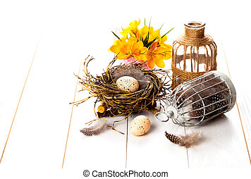Easter eggs nest with birdcage and yellow Spring Crocus on...