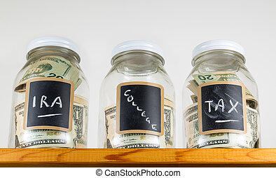 Three glass jars on wooden shelf for savings - Three glass...