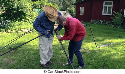 man build gazebo frame - zoom in of two men construct garden...