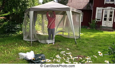 People attach arbour net - People attach protective tent...