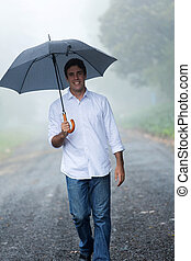 man with umbrella walking in the rain
