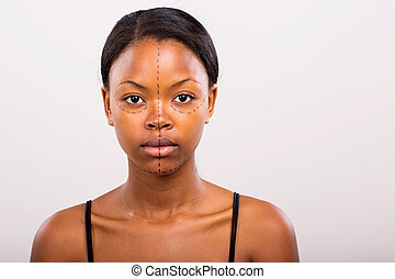 african woman face marked with lines for cosmetic surgery -...