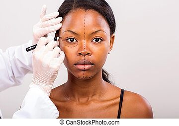 cosmetic surgeon drawing lines on african girl face for...
