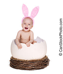 happy baby girl easter rabbit sitting in a giant easter egg in the nest