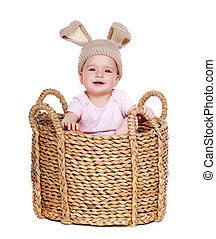 baby girl easter rabbit sitting in a big basket