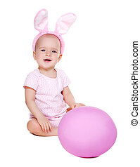 baby girl wearing rabbit ears sitting on the floor with giant pink easter egg