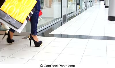 Two beautiful girls with shopping bags come out of the store...