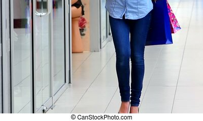 Beautiful girl with shopping bags goes on shopping center.