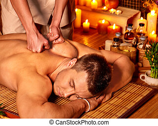 Woman getting bamboo massage. - Man getting massage in spa....