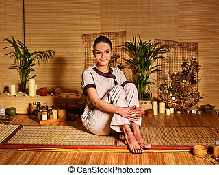 Bamboo massage at spa and woman Sitting on floor