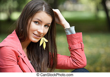 Miss Autumn - Portrait of beautiful girl with leaf in mouth