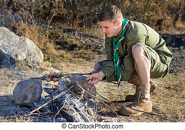 Boy Scout Cooking Sausages on Sticks over Campfire - Boy...