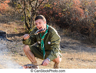 Boy Scout Eating Sausage on Stick by Campfire - Boy Scout...