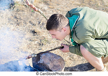 Boy Scout Cooking Sausages Over Campfire - Boy Scout Wearing...