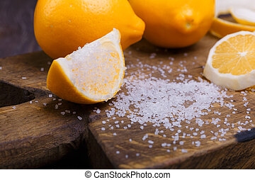 low key lemons - some sliced lemons on a wooden cutting...