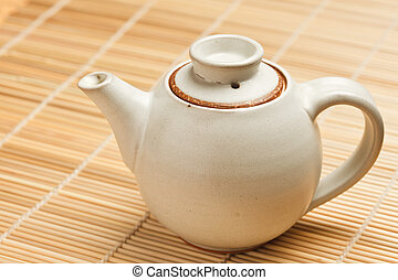 Chinese teapot on bamboo mat close up photo