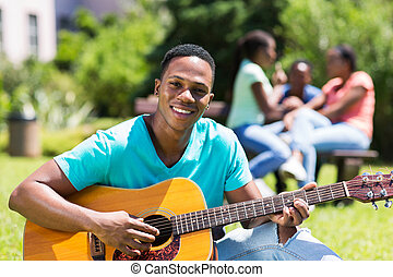 male african college boy playing guitar - handsome male...