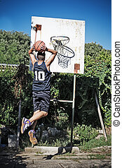 slam dunk in the park - basketball player dunking in the...