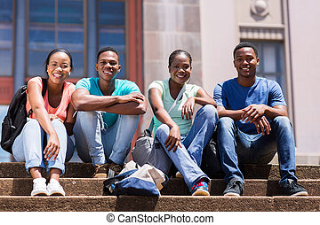 group of african student sitting outside college building -...
