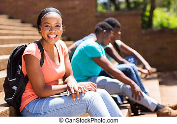 female afro american college student sitting on steps
