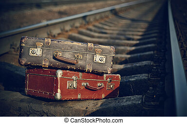 Old suitcases on rails - Two old suitcases lie on railway...