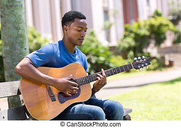young african college student playing guitar outdoors