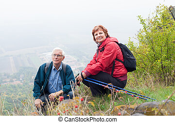 Senior couple hiking and resting in nature
