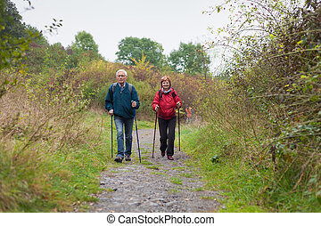 Senior couple Nordic walking on the trail in nature - Senior...
